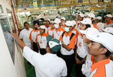 Listening attentively to an explaination on the painting process in Honda's manufacturing plant.