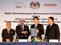 Datuk Suret Singh exchanging MOU with Atsushi Fujimoto witnessed by Dato' Haji Zakaria and Azman Idris.