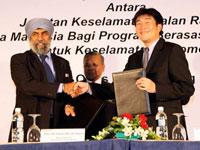 Datuk Suret Singh exchanging MOU with Atsushi Fujimoto witnessed by Dato' Haji Zakaria.