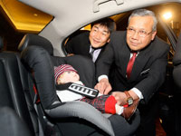 Dato' Haji Zakaria fastening the Honda child seat wtih Atsushi Fujimoto.