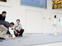 ASIMO plays futsal with one of the online contest winner.