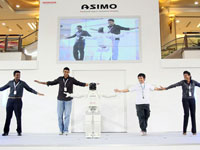 ASIMO demonstrates his flexibility by dancing with the crowd.