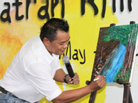 Encik. Zainal Abidin autographing his art piece during the Rhino Essay and Photo Contest prize giving ceremony.