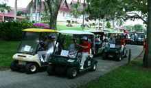 Participants and HMSB VIPs arriving at the golf course in golf buggies.