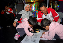 Children coloring their art piece while parents looked on.